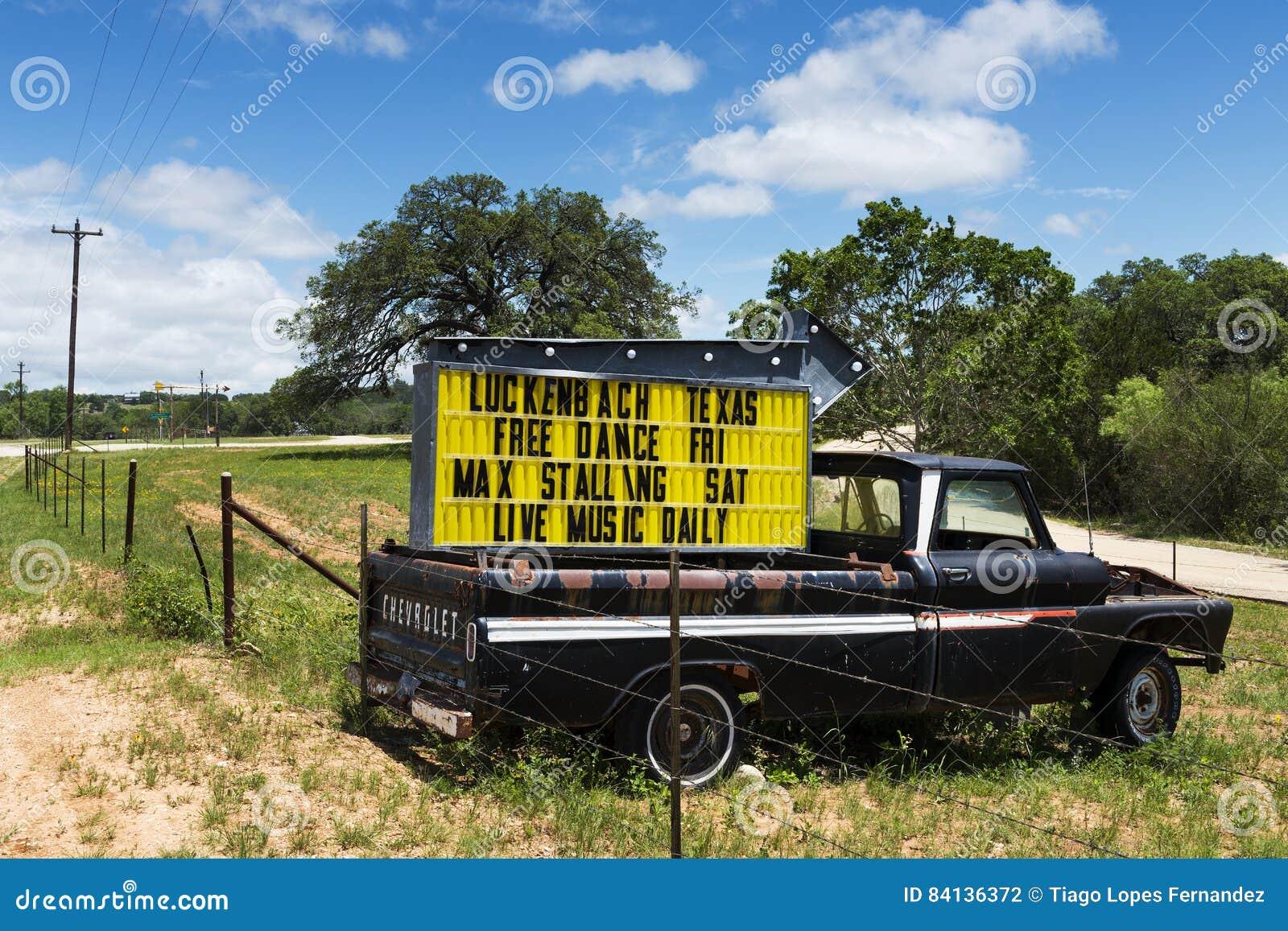 Oude vrachtwagen met een teken voor een muziekgebeurtenis in Luckenbach, Texas, de V.S.