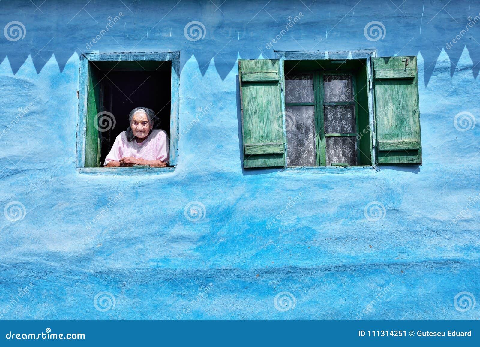 Oude vrouw bij het venster in oud traditioneel blauw huis
