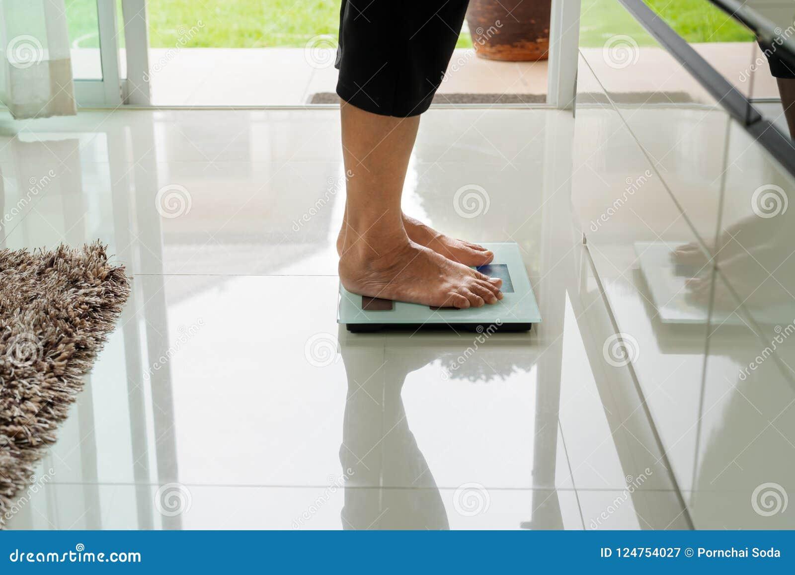 Oude vrouw die zich op gewichtsschaal bevinden in woonkamer