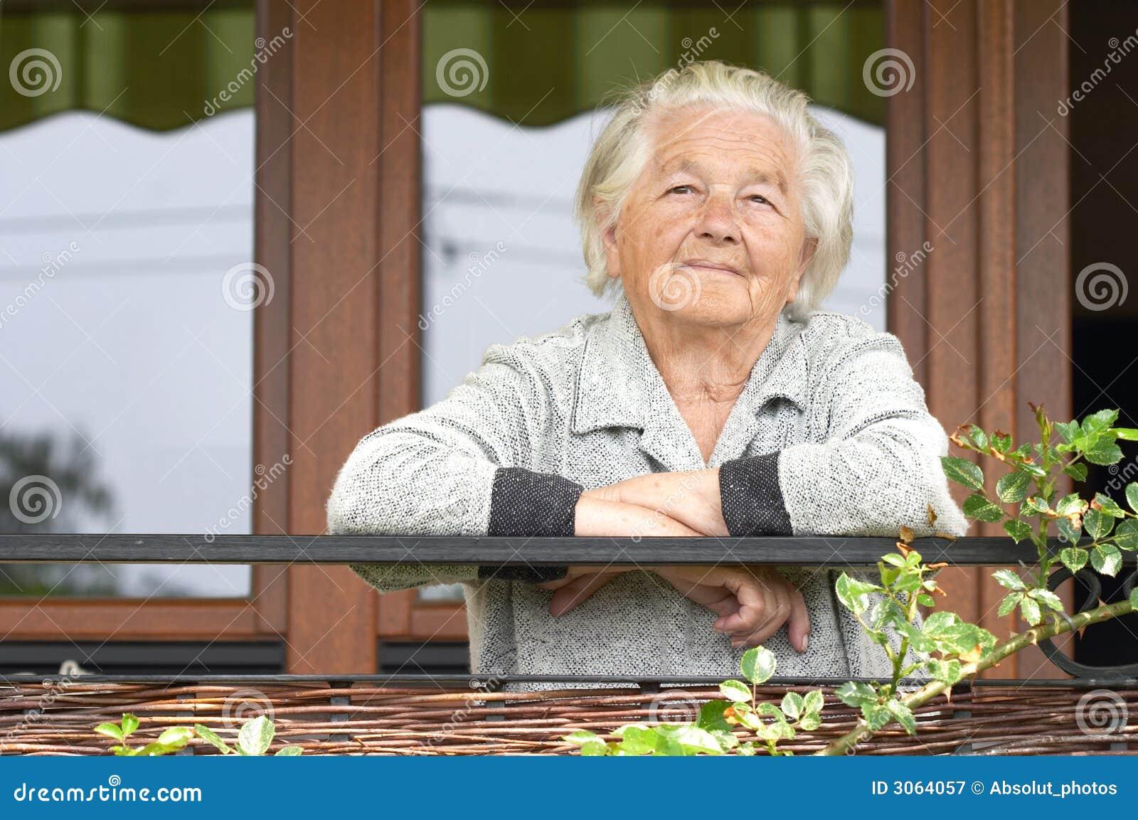 Oude vrouw op de portiek