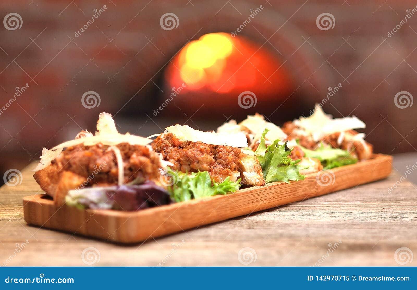 Oude wereld Italiaanse bruschetta die met vleessaus en kaas wordt bedekt
