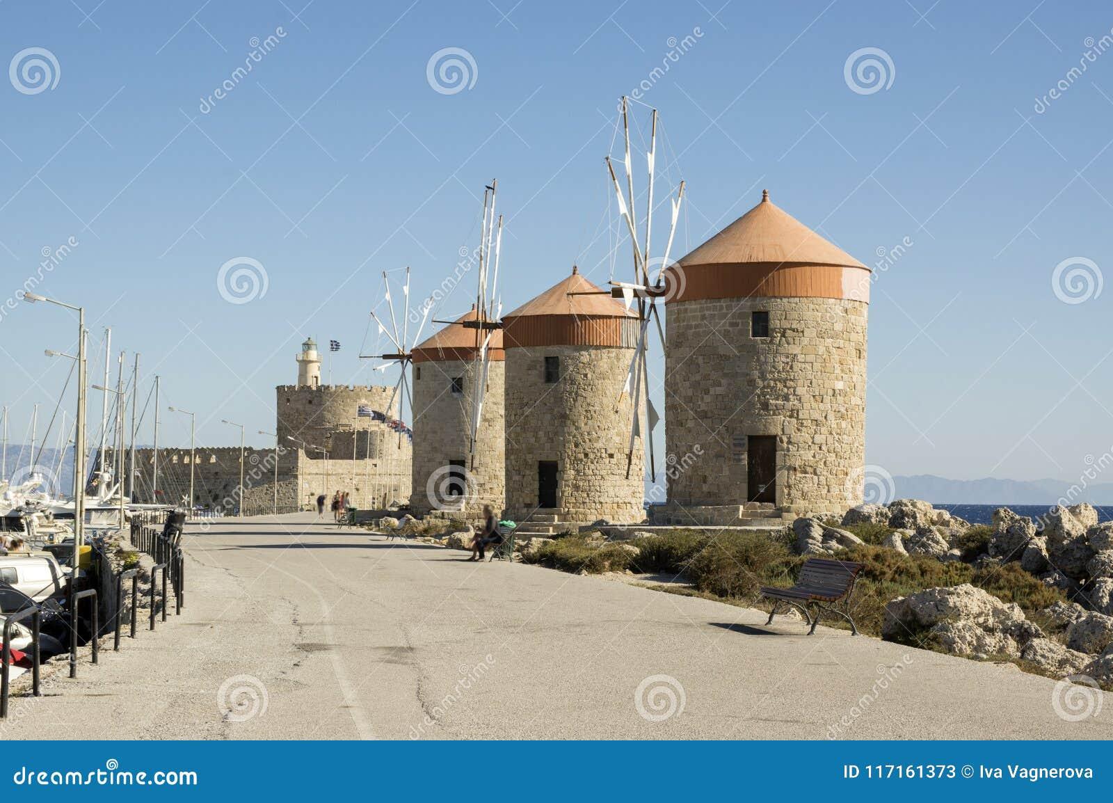Oude windmolens op de steenachtige kustlijn van Rhodos in haven, oude historische gebouwen, bezienswaardigheid, blauwe hemel