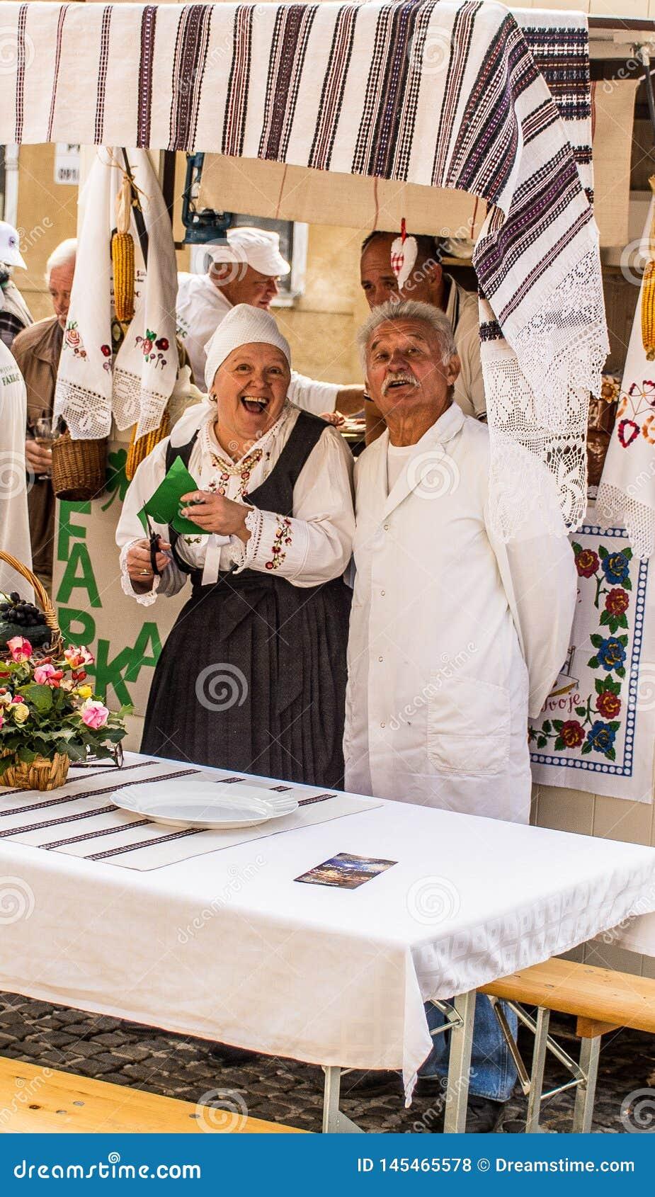 Ouder paar dat traditionele maaltijd en douane op een Samobor-viering van de stedendag voorstelt