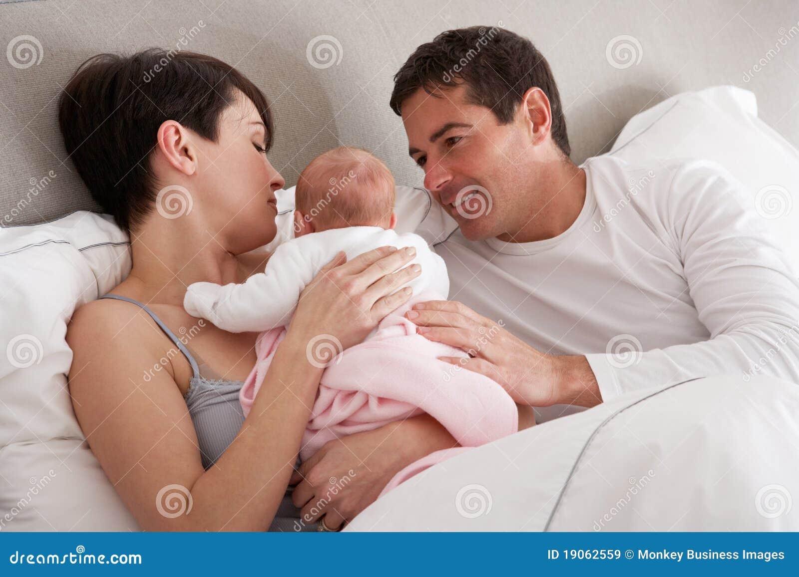 Ouders die Pasgeboren Baby in Bed knuffelen