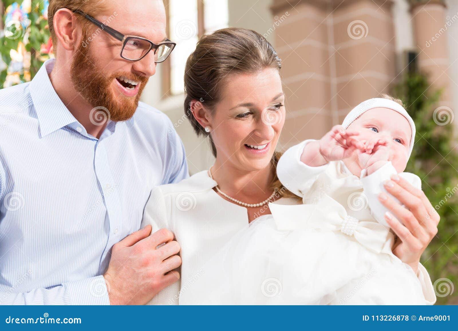 Ouders met baby bij doopsel in kerk