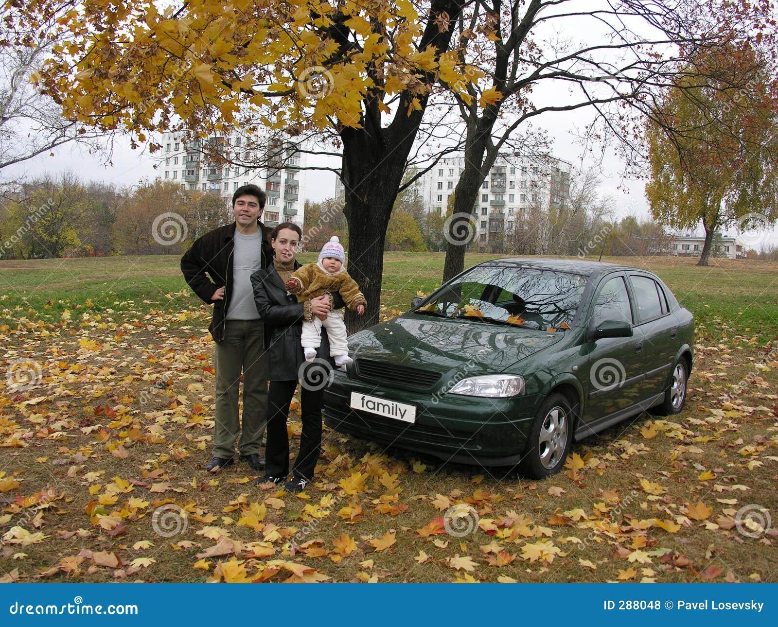 Ouders met baby en auto en de herfst