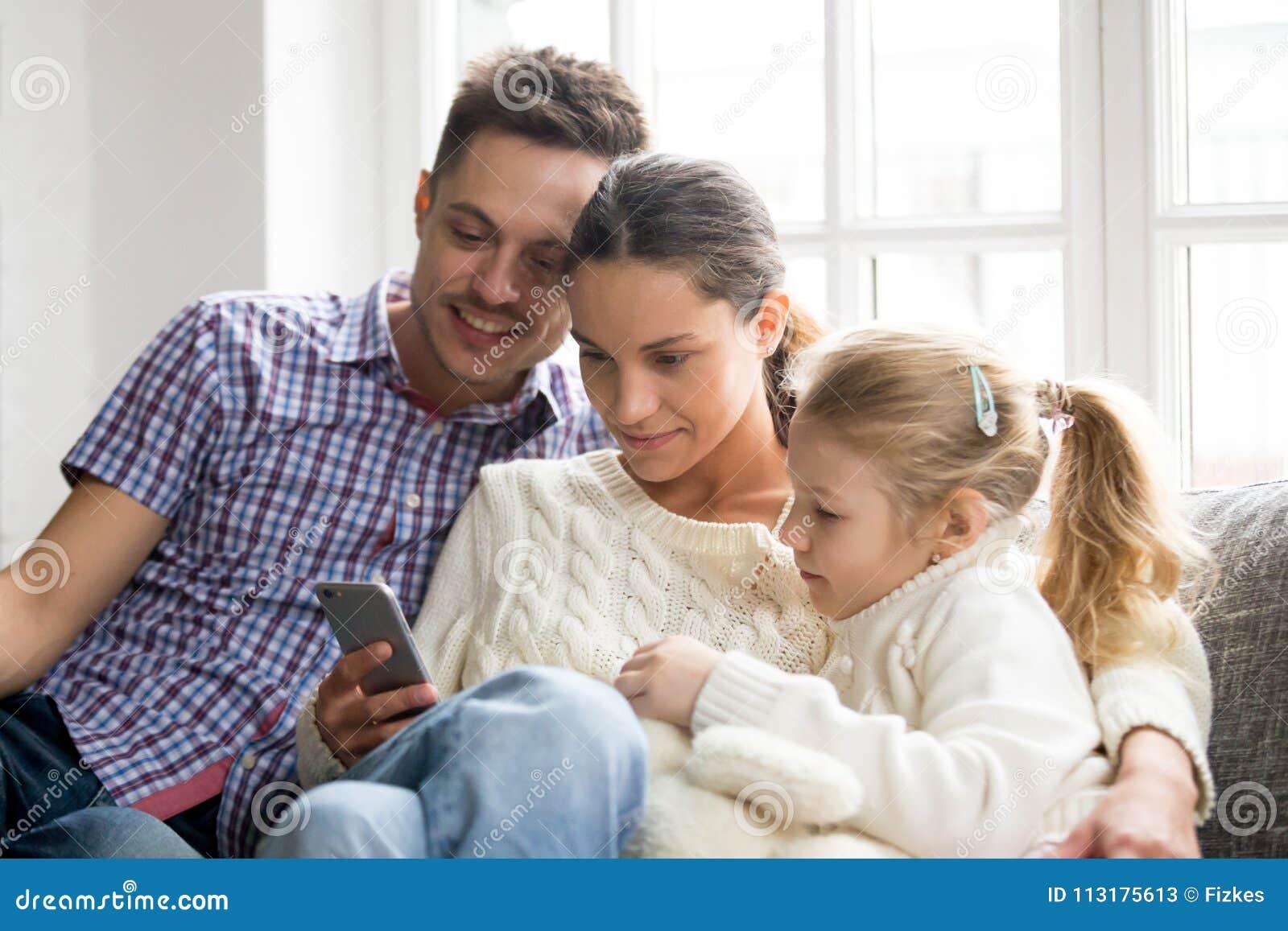 Ouders met dochter het letten op video op mobiele telefoon thuis