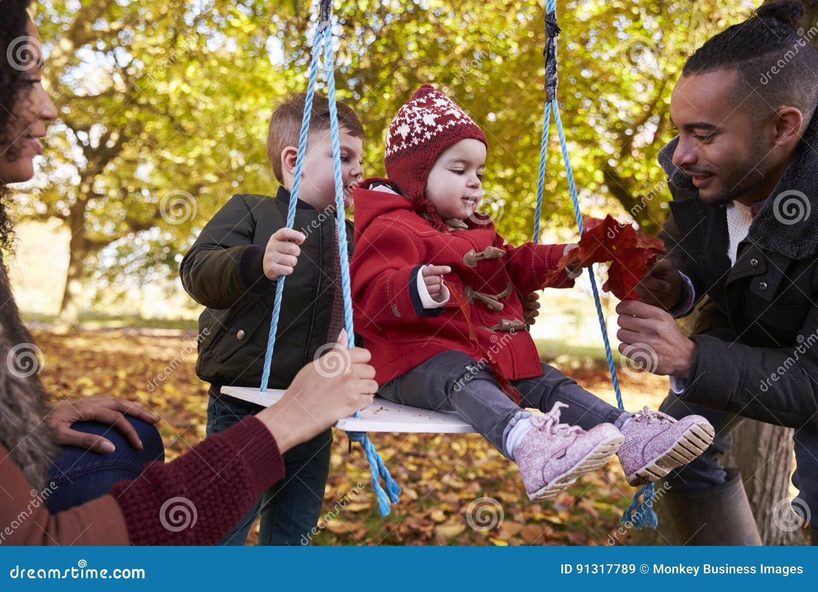 Ouders met Kinderen die op Boomschommeling spelen in Autumn Garden