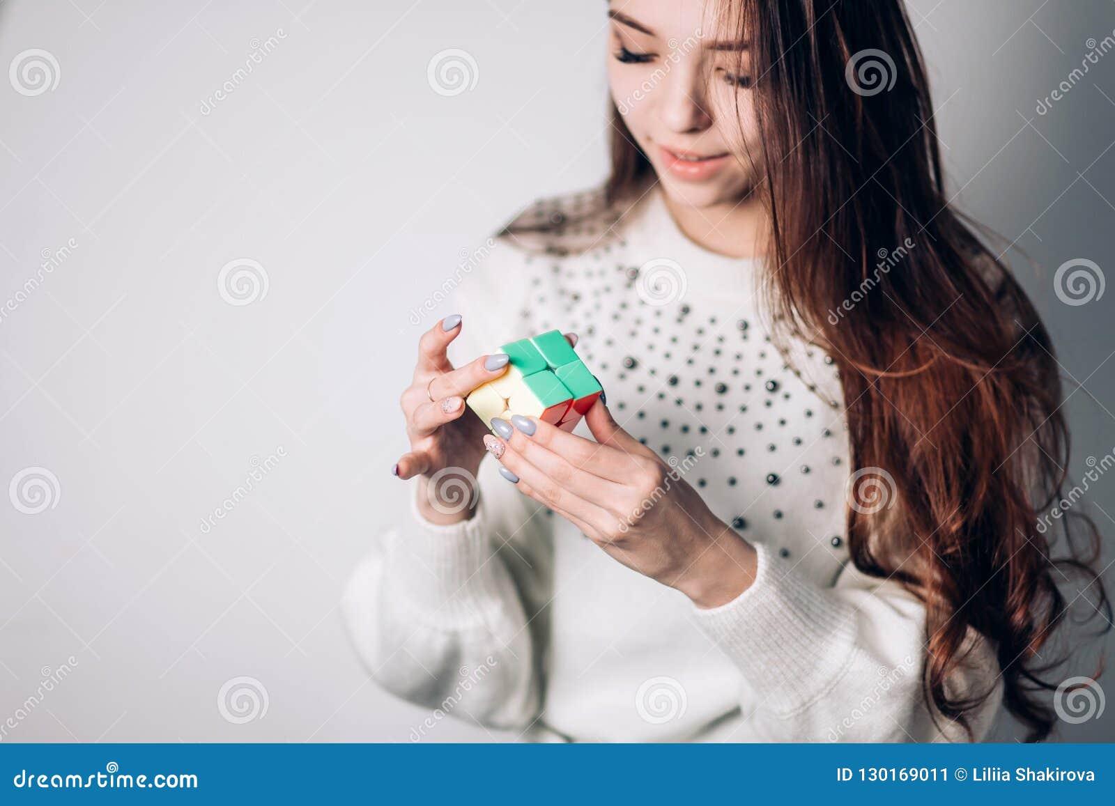 OUFA, RUSSIE - 14 JANVIER 2018 : Une femme attirante de brune avec de longs cheveux résout un puzzle, le cube d un Rubik bilatéra