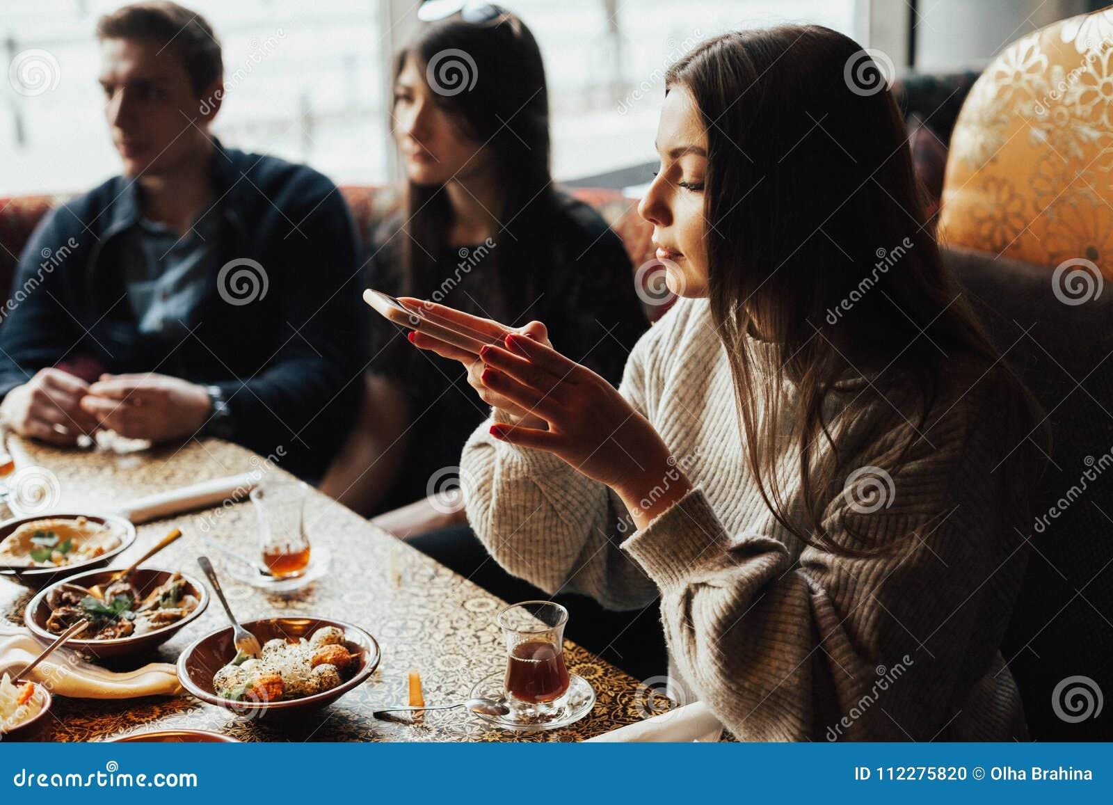 Oung dziewczyna bierze obrazki jedzenie Młoda firma ludzie dymi nargile i komunikuje w orientalnej restauraci L