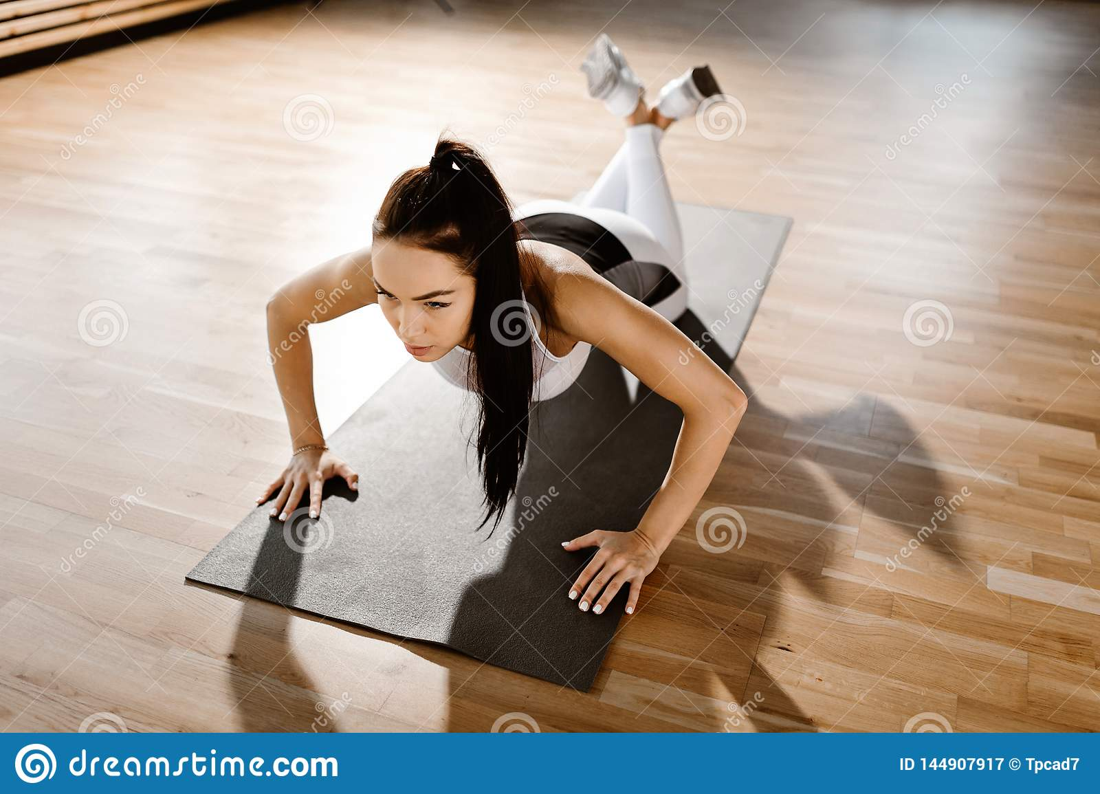 Oung slim dark-haired girl dressed in white sports clothes is doing push ups in the gym