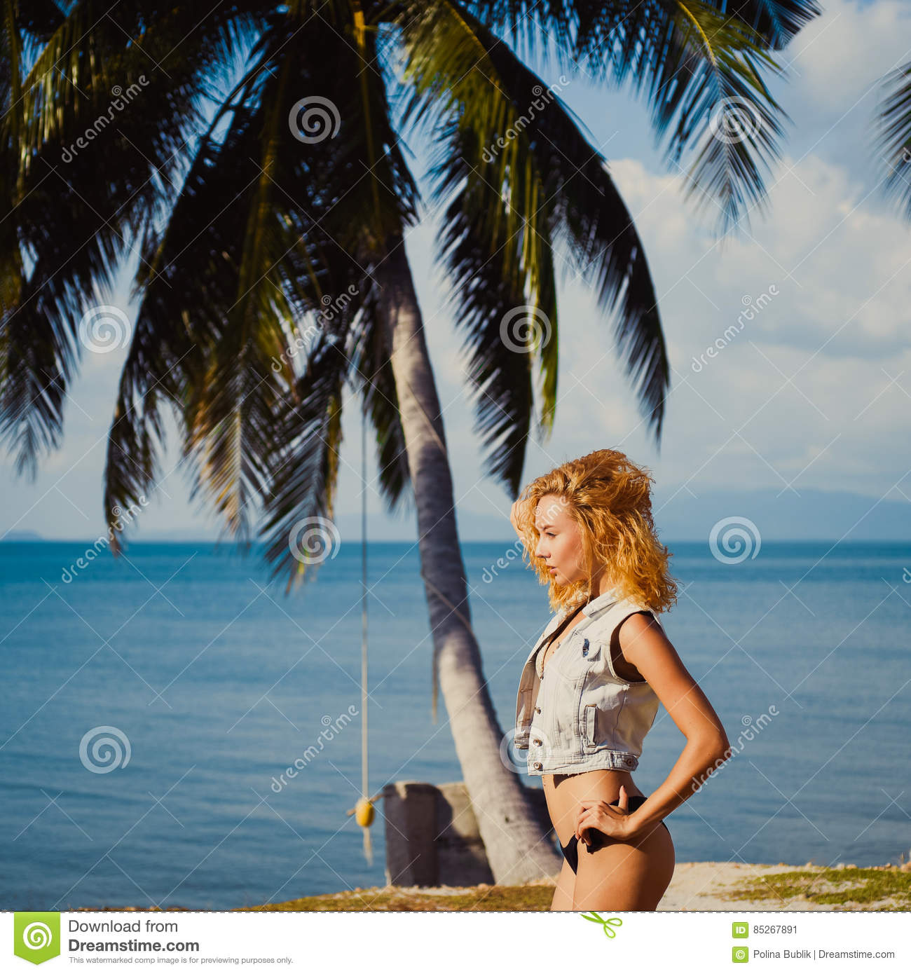 Oung tan slim redhead girl on background of blue sky in the summer sea palm