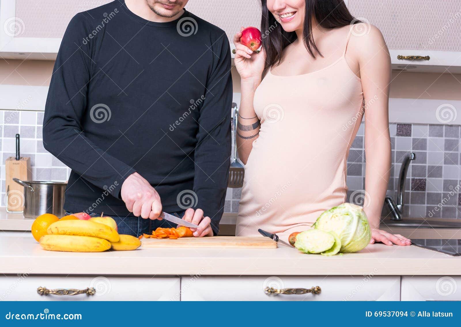 Ouple de ¡ de Ð préparant la nourriture dans la cuisine Femme enceinte