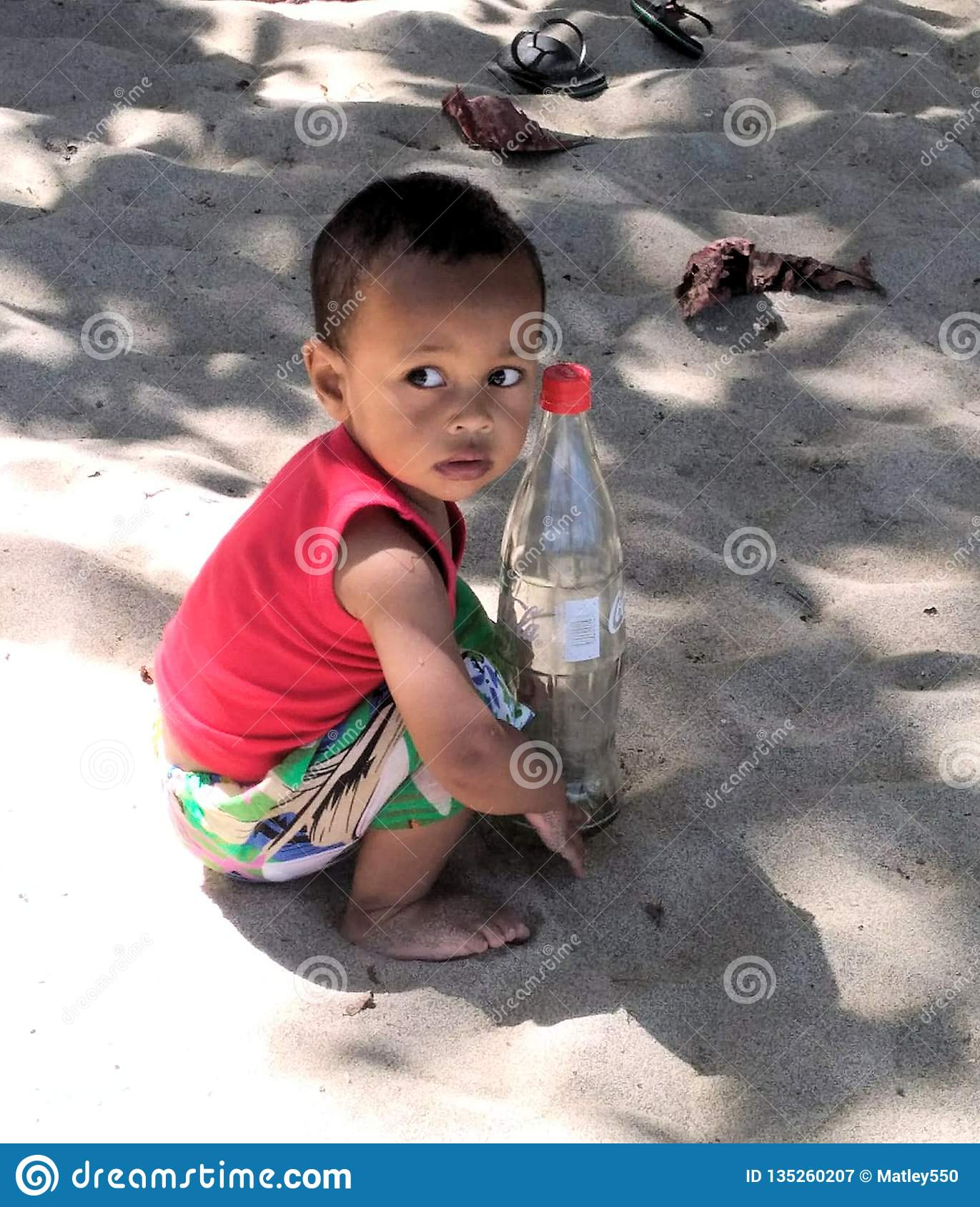Nosy Be, Madagascar - 09/21/2018: An African child with a melancholy look holding a bottle of coke in his hands