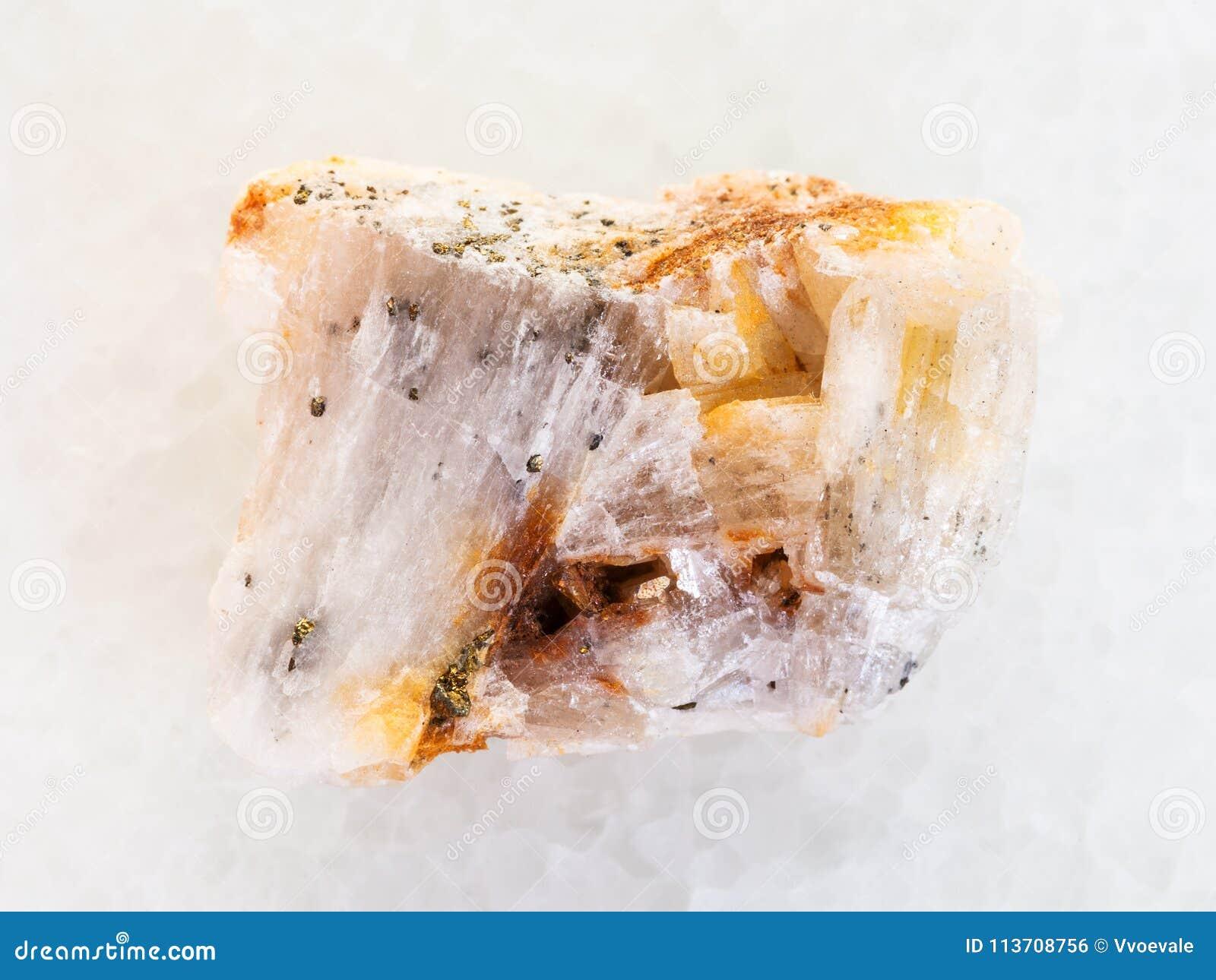 Ouro nativo na pedra áspera de quartzo no mármore branco