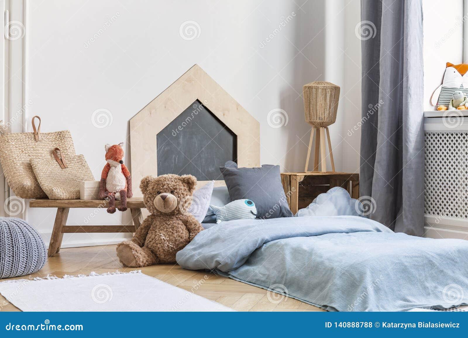 Ours de nounours à côté d un lit couvert de feuilles bleues dans un intérieur naturel de pièce d enfant Photo réelle
