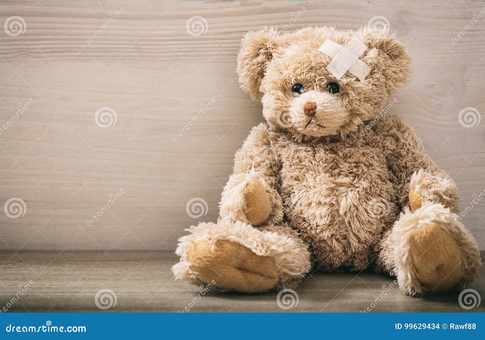 Ours de nounours avec le bandage sur un plancher en bois