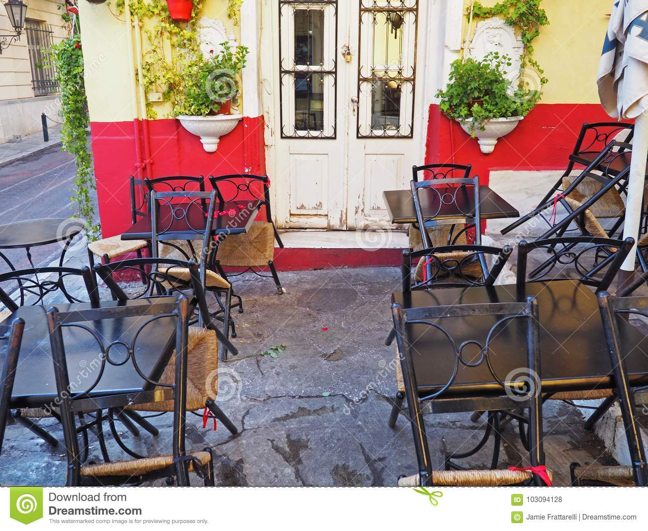 Chairs lean against tables at a closed taverna in the morning in athens greece
