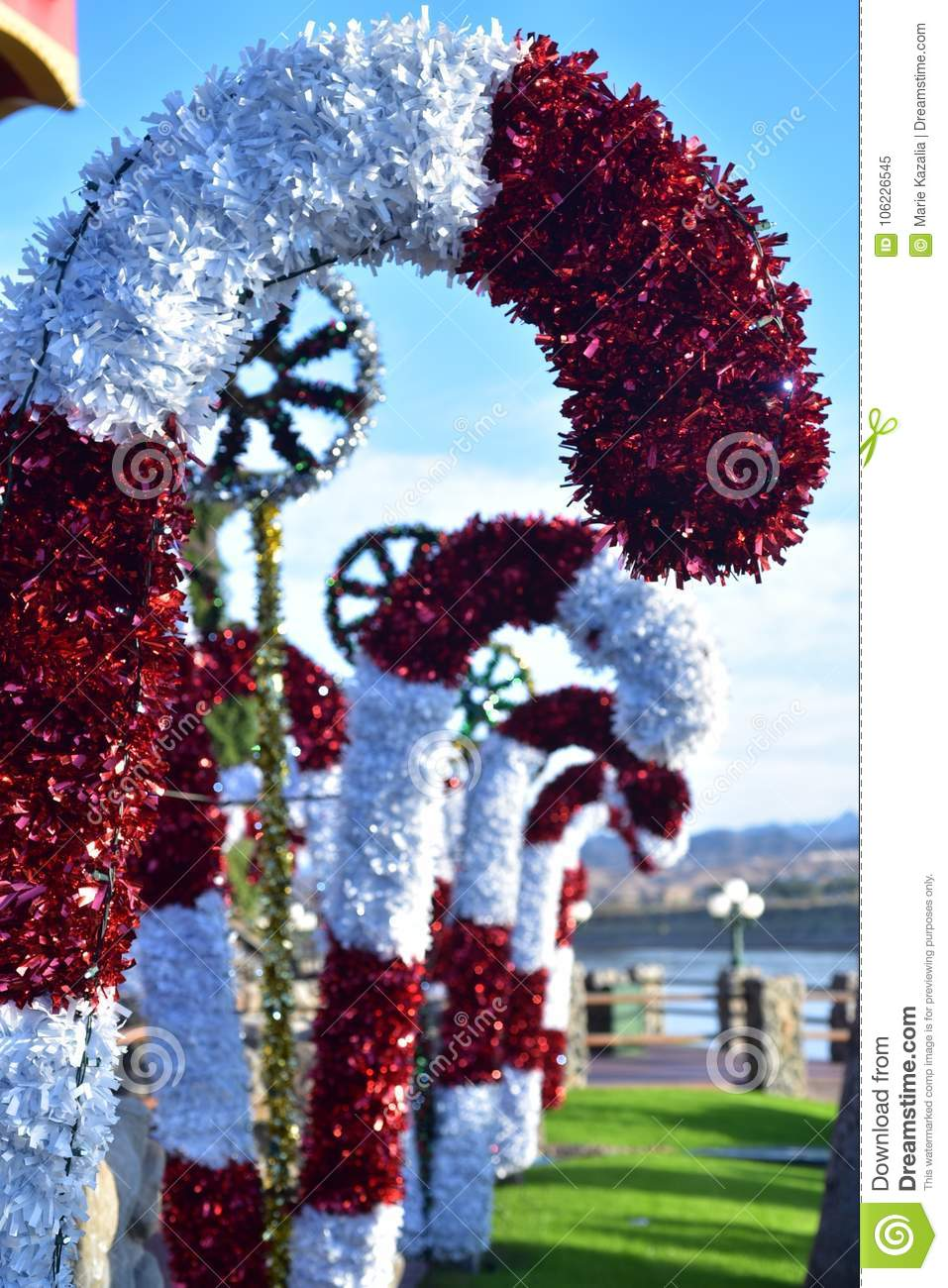 outdoor christmas decorations with large candy canes and gods eyes in south west desert landscape with palm trees in background in arizona usa