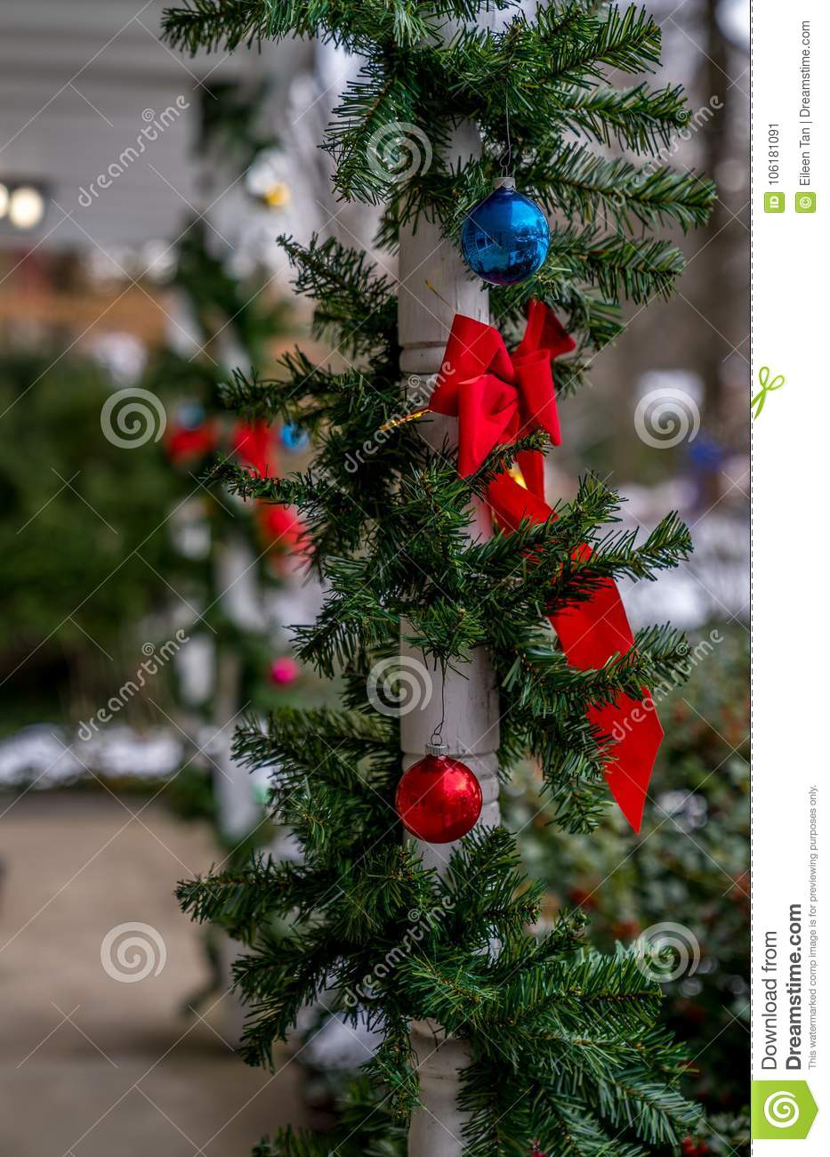rad bow tie christmas ornaments and evergreen decoration hang on the wood column traditional celebration winter holiday season and christmas concept