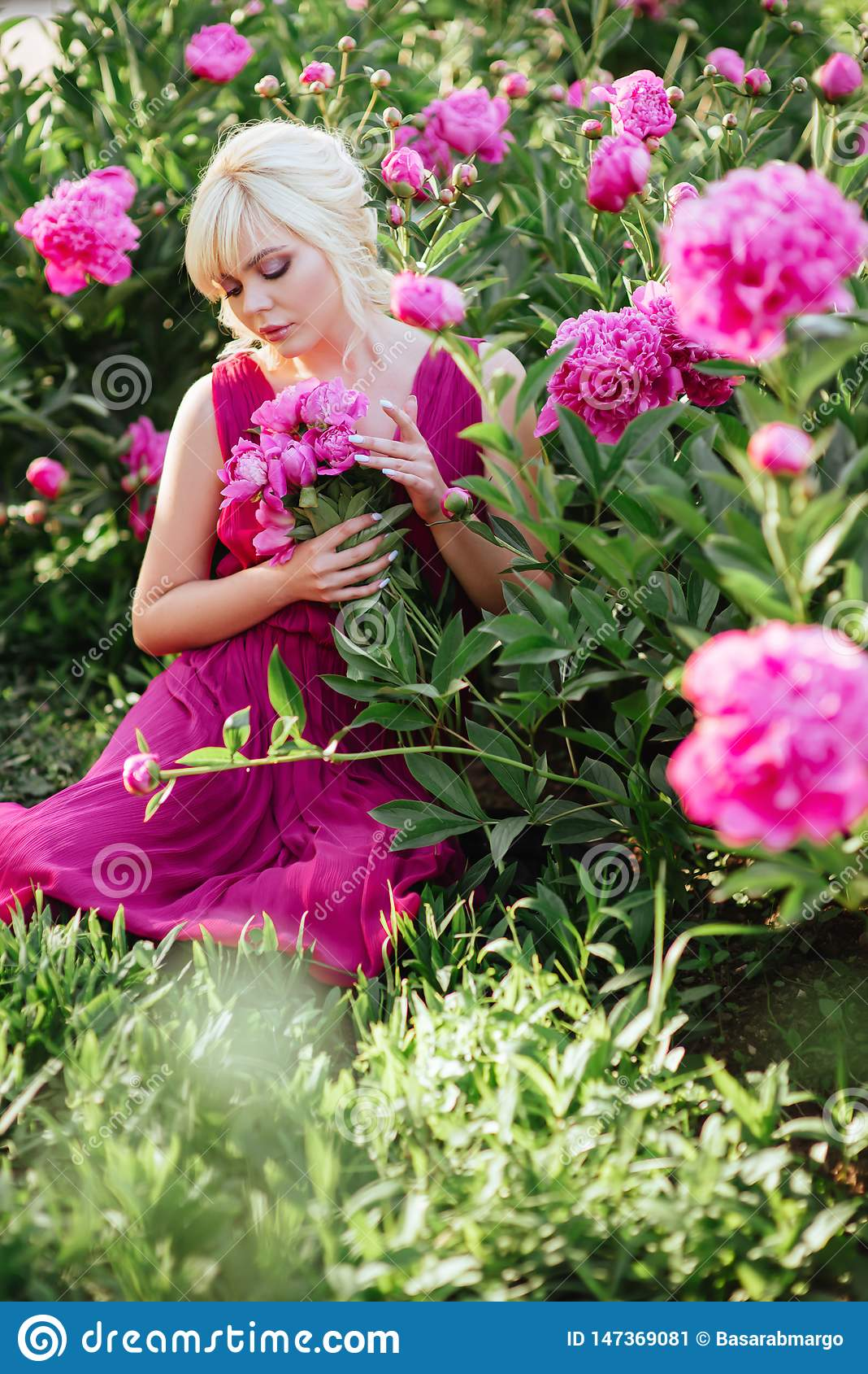 Outdoor close up portrait of beautiful young woman in the blooming garden. Female spring fashion concept