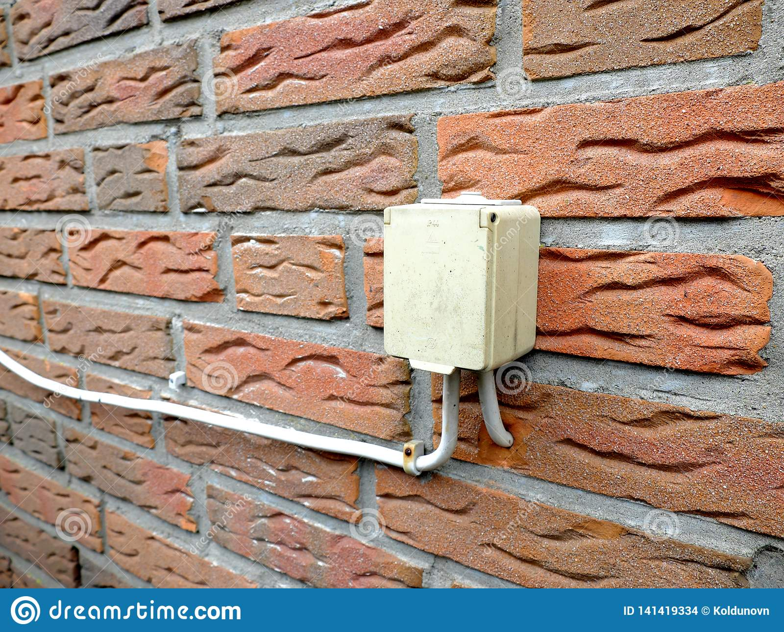 Outdoor electrical socket is mounted on the brick wall