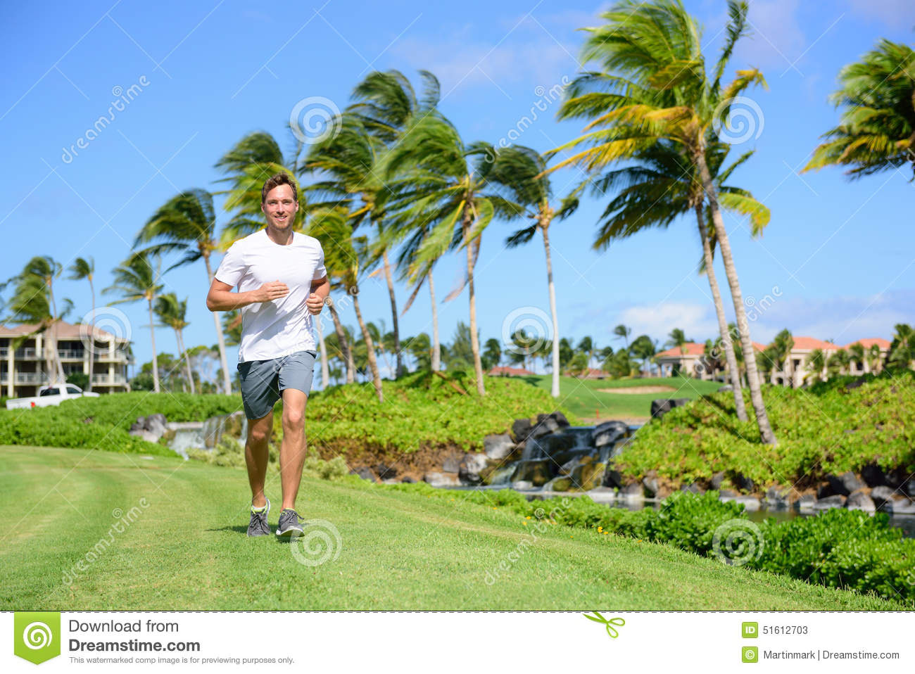Outdoor exercise man running on grass in city park