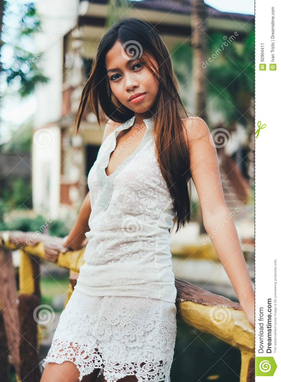 Outdoor fashion portrait of young pretty happy woman in summer outfit posing in luxury resort . Holiday vacation mood