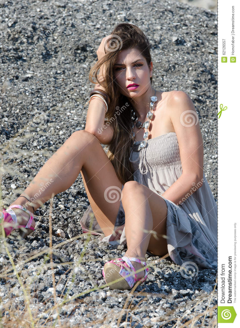 Outdoor fashion shoot sitting on rocky ground