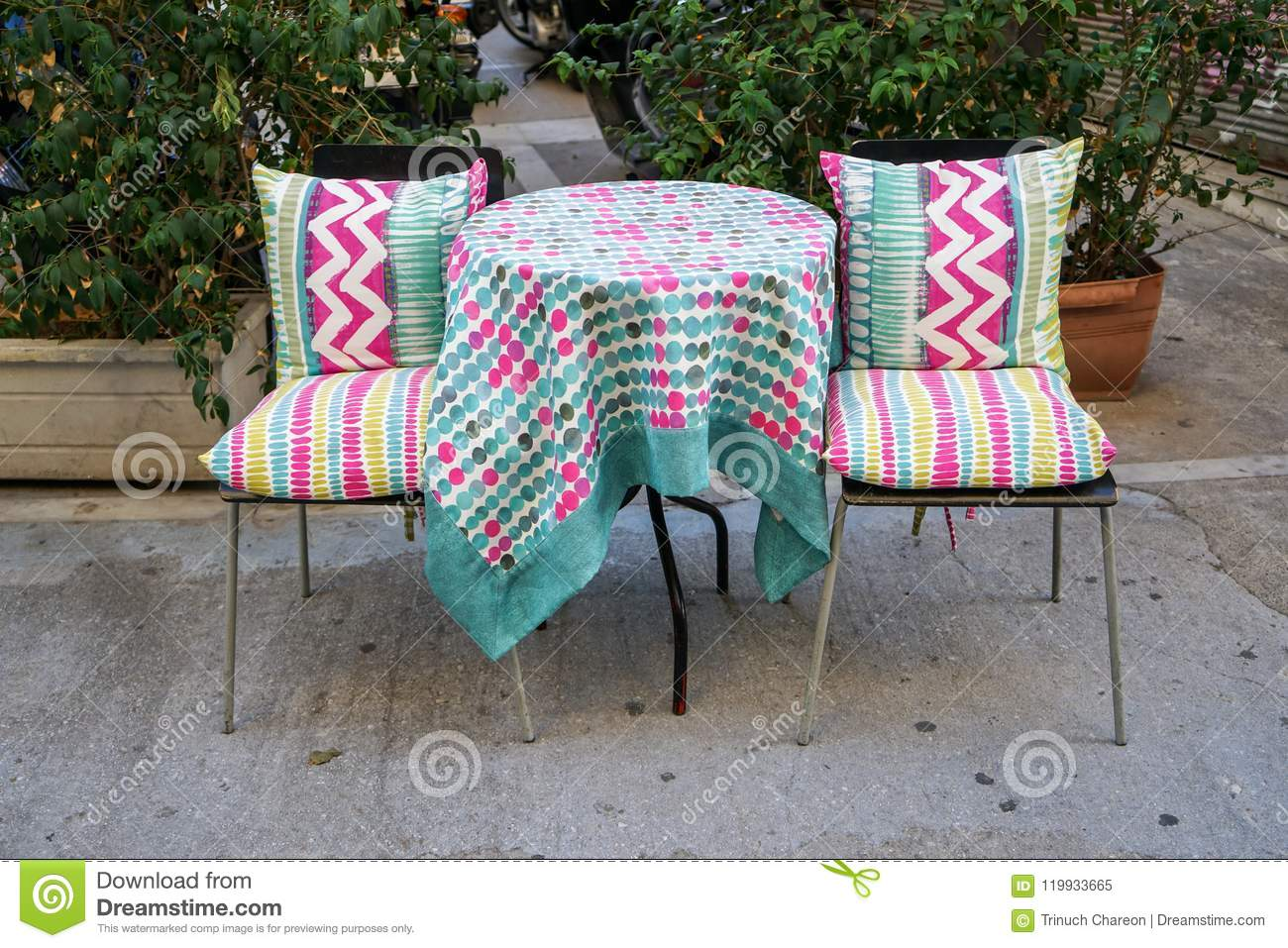 Outdoor furniture round table and chairs with colorful pattern fabric table cloth on concrete floor