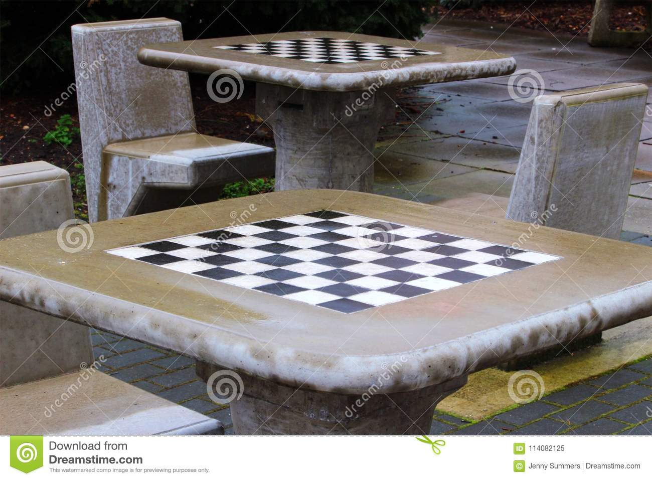 Outdoor Games Area After An April Shower. Chequered Concrete Chess Tables  And Chairs Slowly Drying Out, Waiting For Lunchtime Gamers