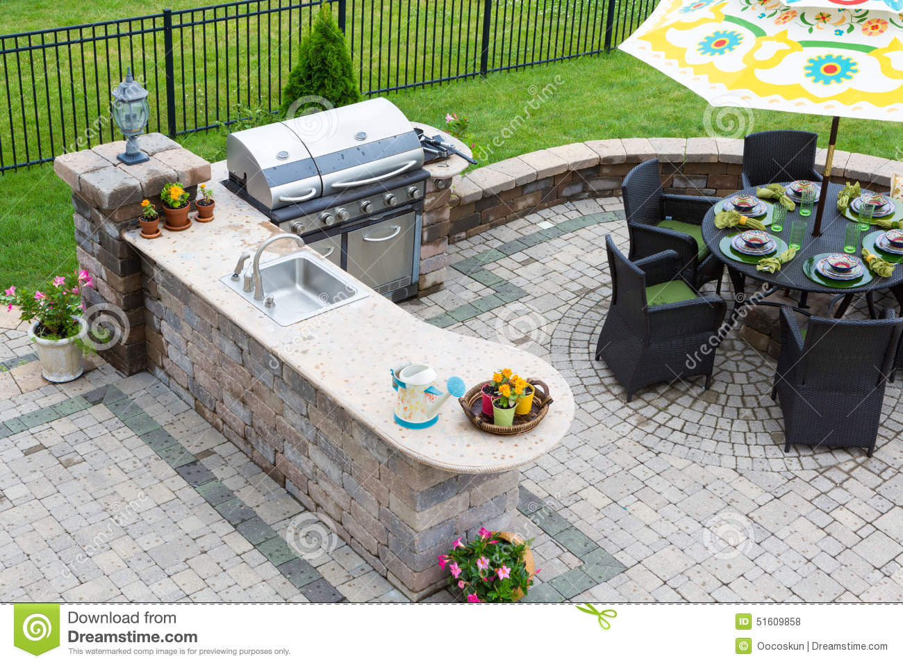 angle view of a stylish outdoor kitchen, gas barbecue and dining table ...