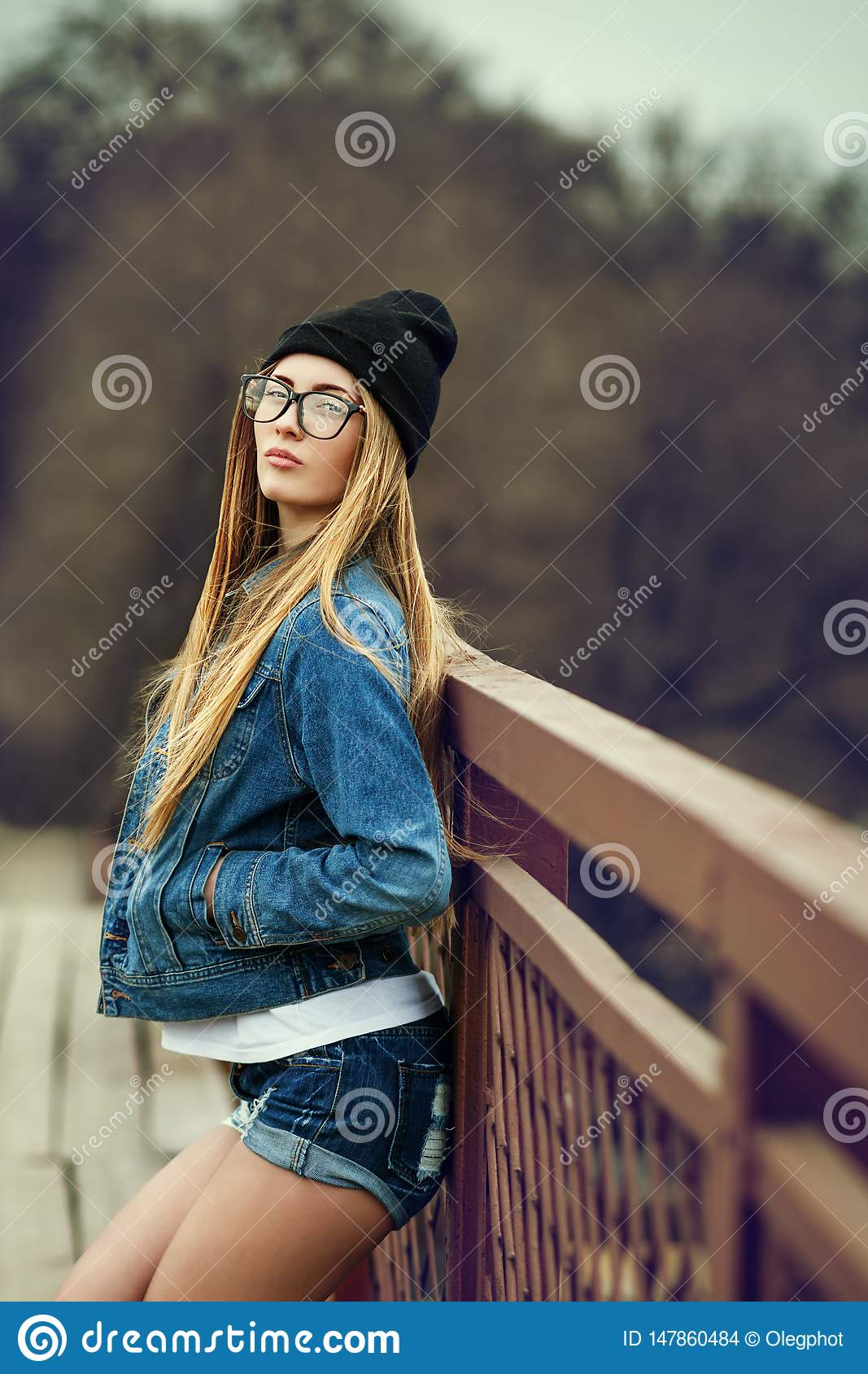 Outdoor lifestyle portrait of pretty young girl, wearing in hipster swag grunge style urban background. Retro vintage toned image