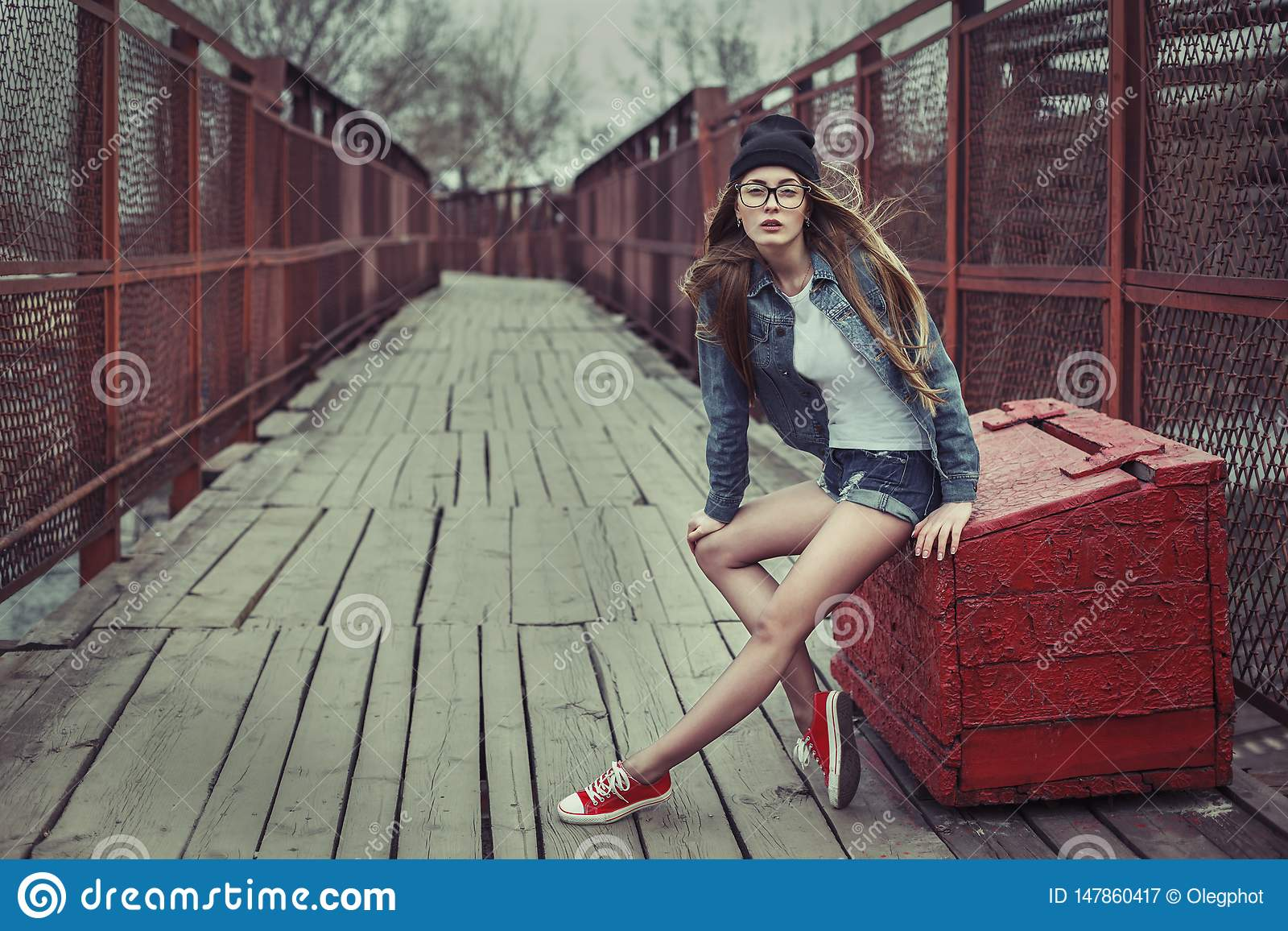 Outdoor lifestyle portrait of pretty young sitting girl, wearing in hipster swag grunge style urban background. Retro vintage