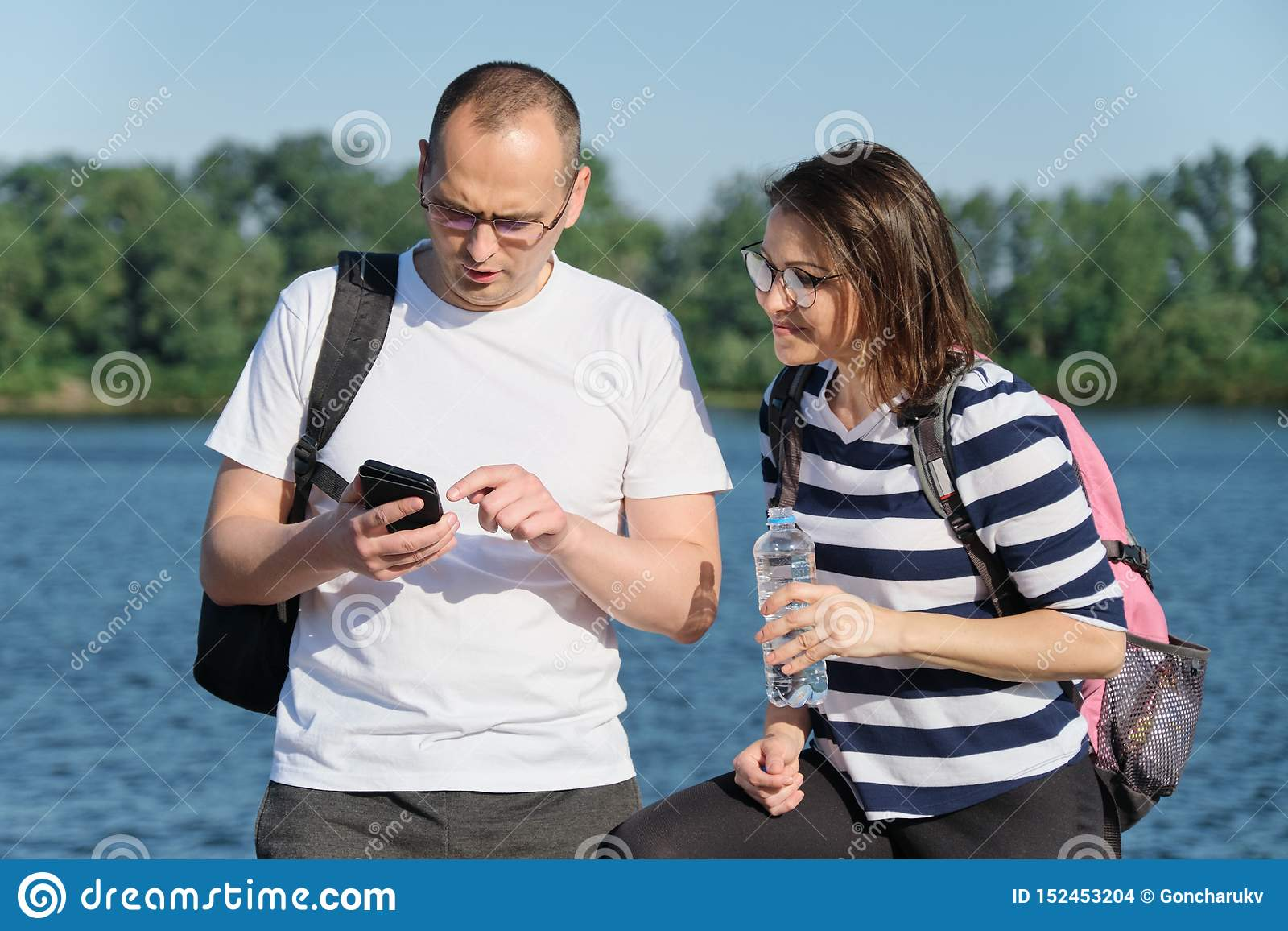Outdoor mature couple using smartphone, man and woman talking walking in the park