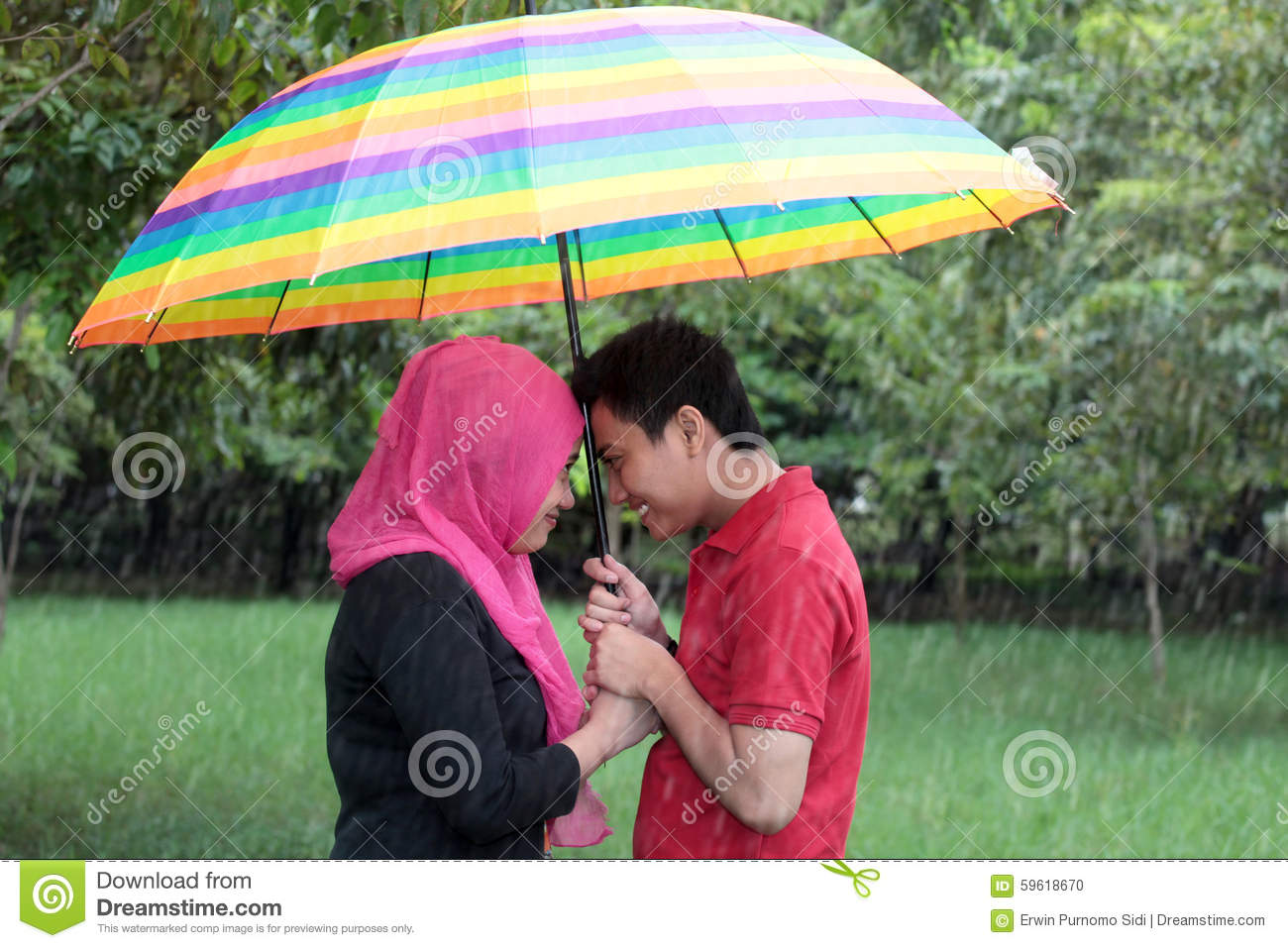 Outdoor muslim asian couple in the rain with umbrella stock photo