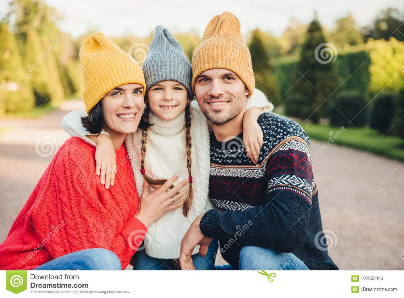 Outdoor portait of beautiful brunette female, handsome man, pretty small girl embrace together, have pleasant mood, walk in park,