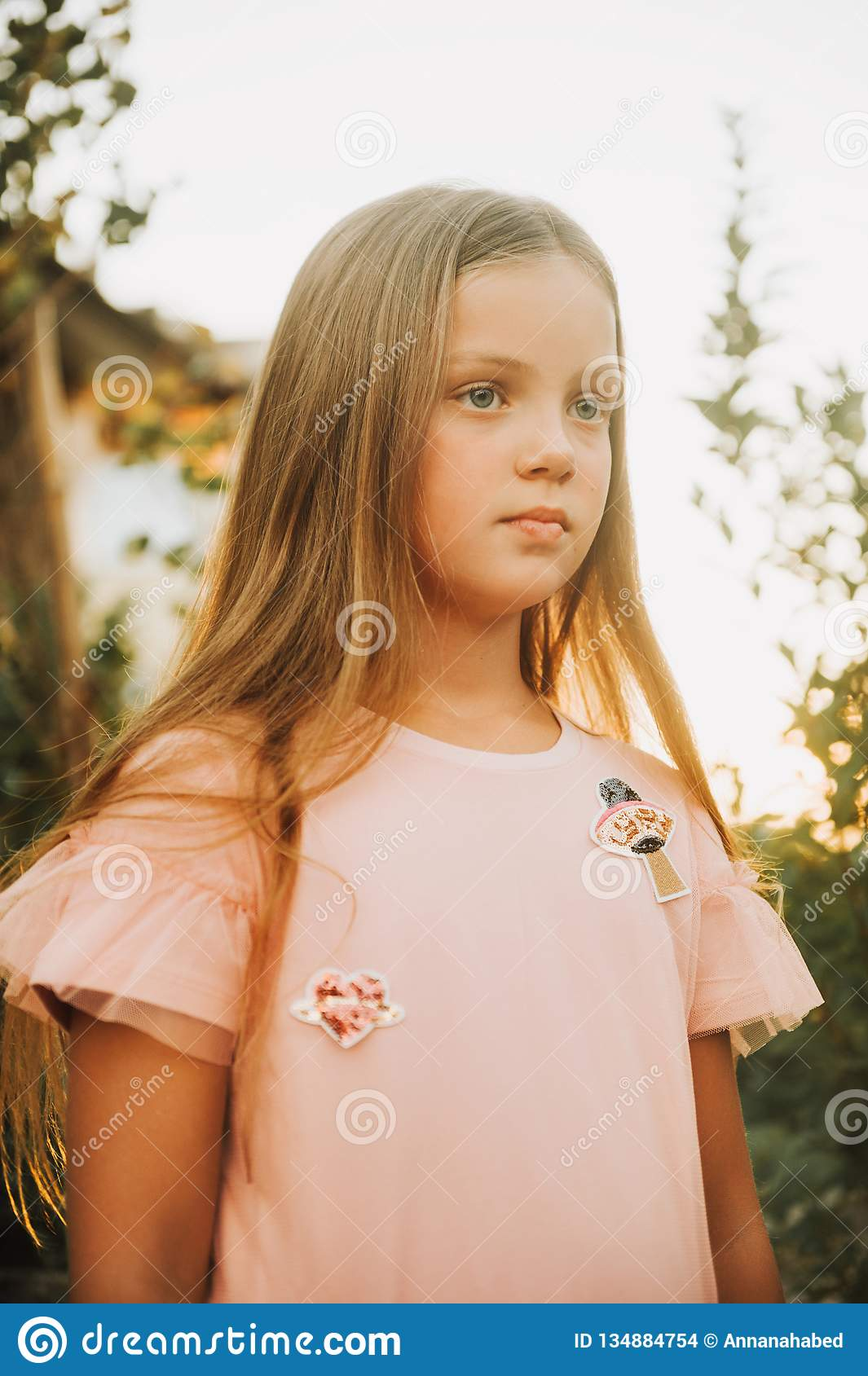 8d5401a4e32bf Outdoor portrait of beautiful little girl with long blonde hair wearing  pink dress, posing in sunset light. More similar stock images
