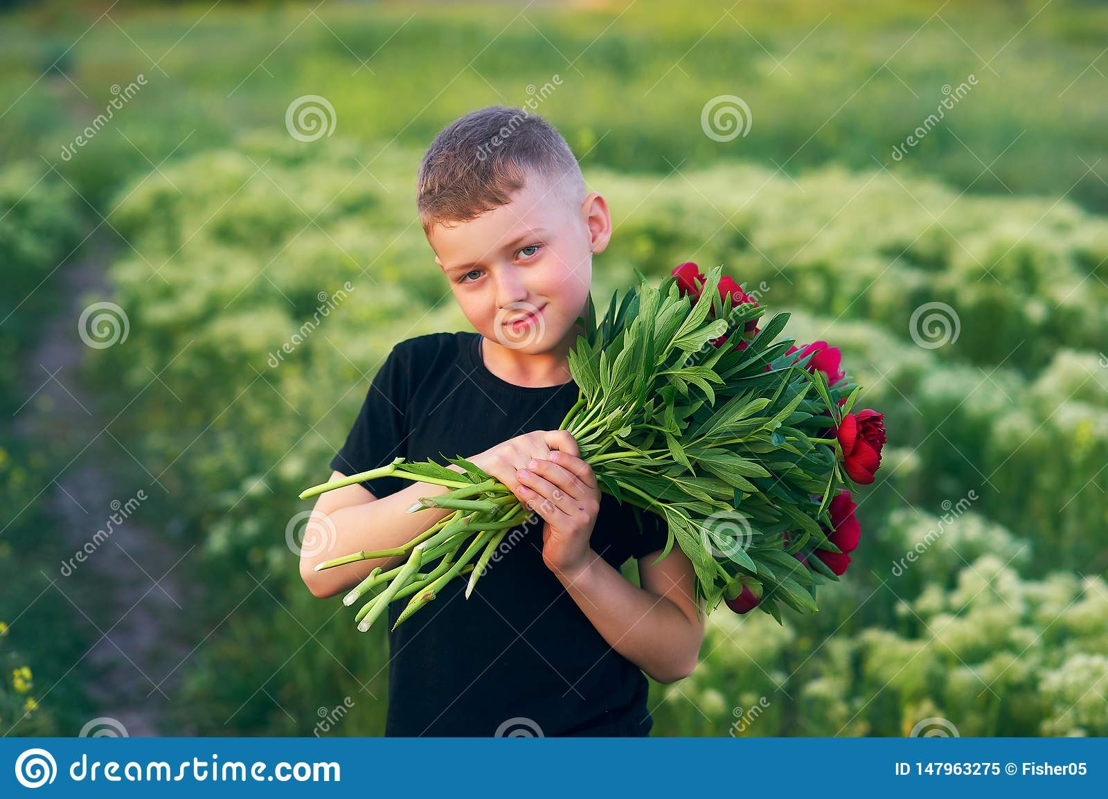 Outdoor portrait of a boy on a walk with peony flowers
