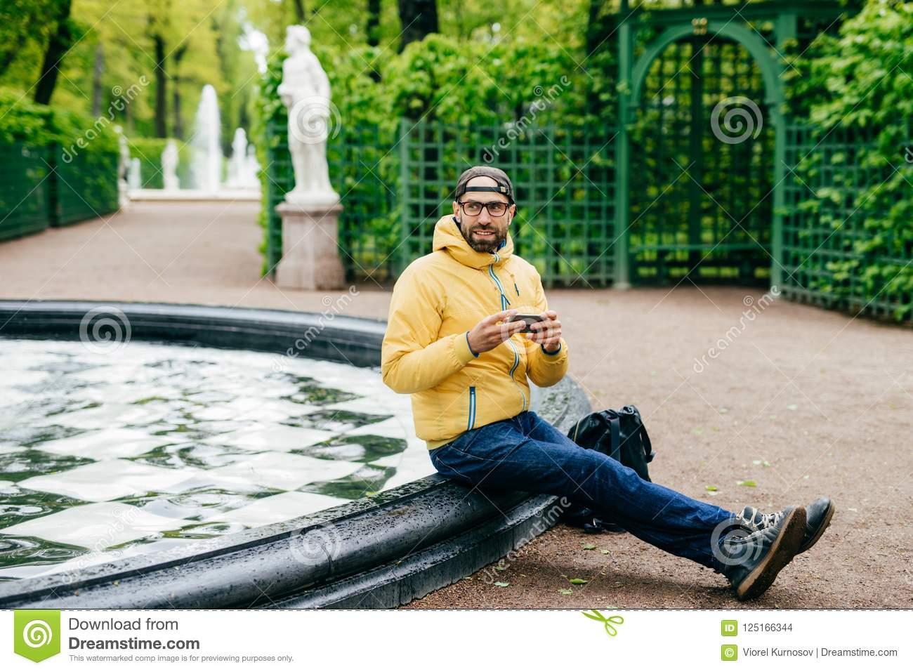 Outdoor portrait of bushy man wearing cap, jacket, jeans and eyeglasses having rest near fountain holding his modern device in han