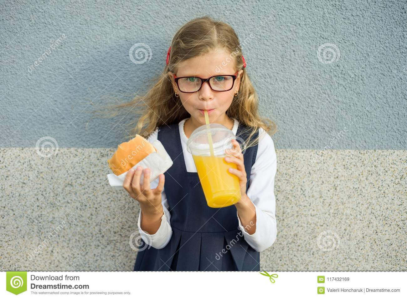 Outdoor portrait of child girl with blond curly hair with glasses. Girl eats sandwich and drinks orange juice.