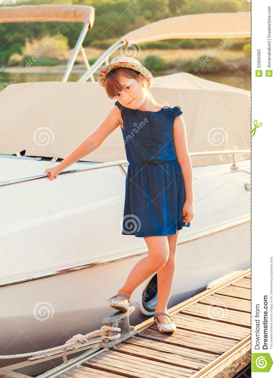 fd905f79a Sunset portrait of a cute little girl, standing by the lake next to white  yacht, wearing blue, dress and colorful hat