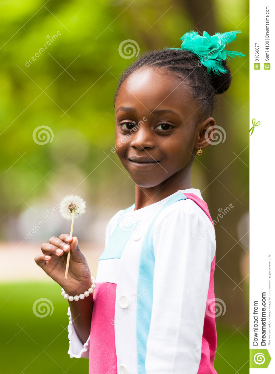 young blakc Outdoor portrait of a cute young black girl holding a dandelion