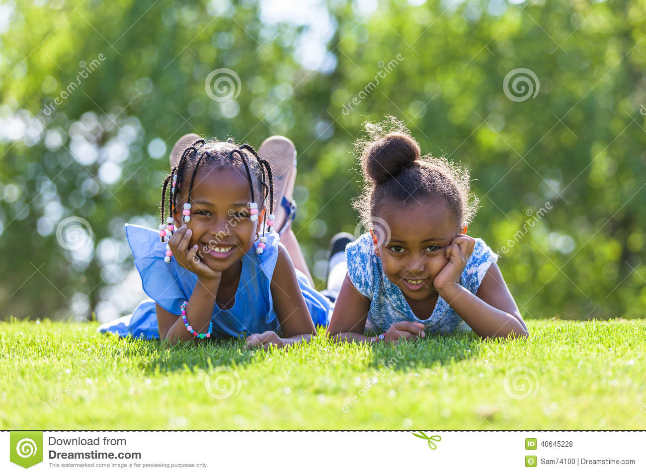 Outdoor Portrait Of A Cute Young Black Sisters Lying Down