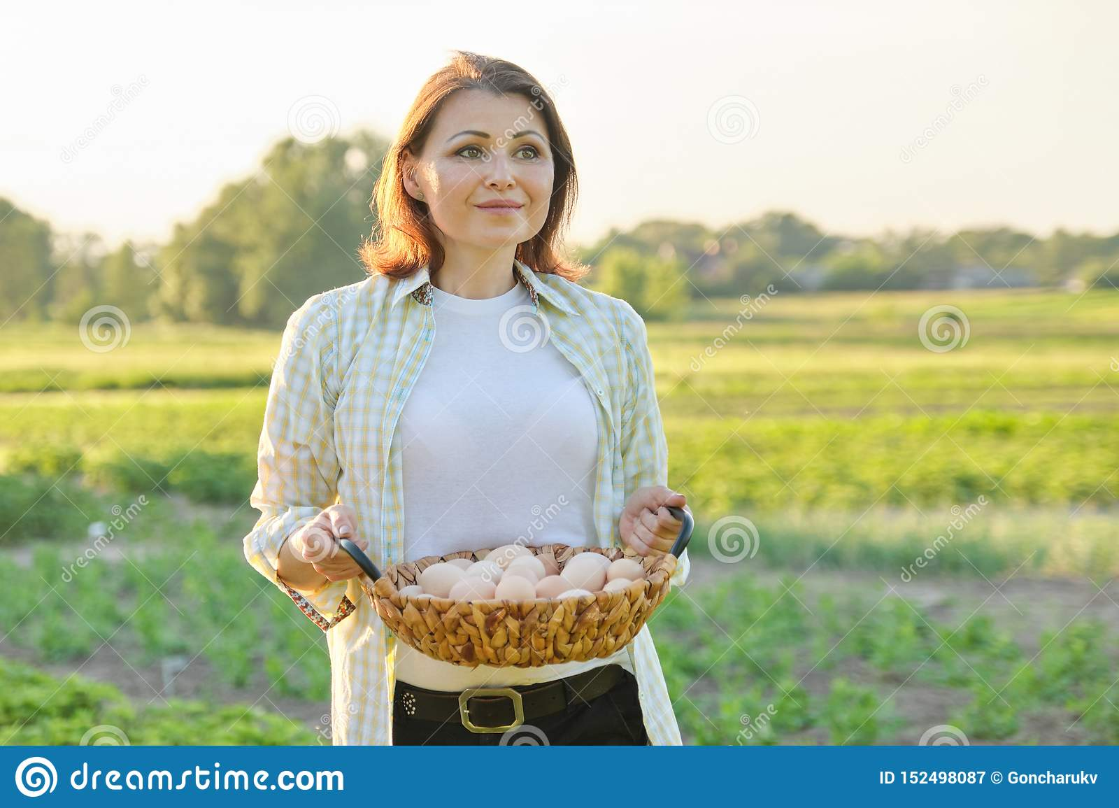 Outdoor portrait of farmer woman with basket of fresh chicken eggs, farm