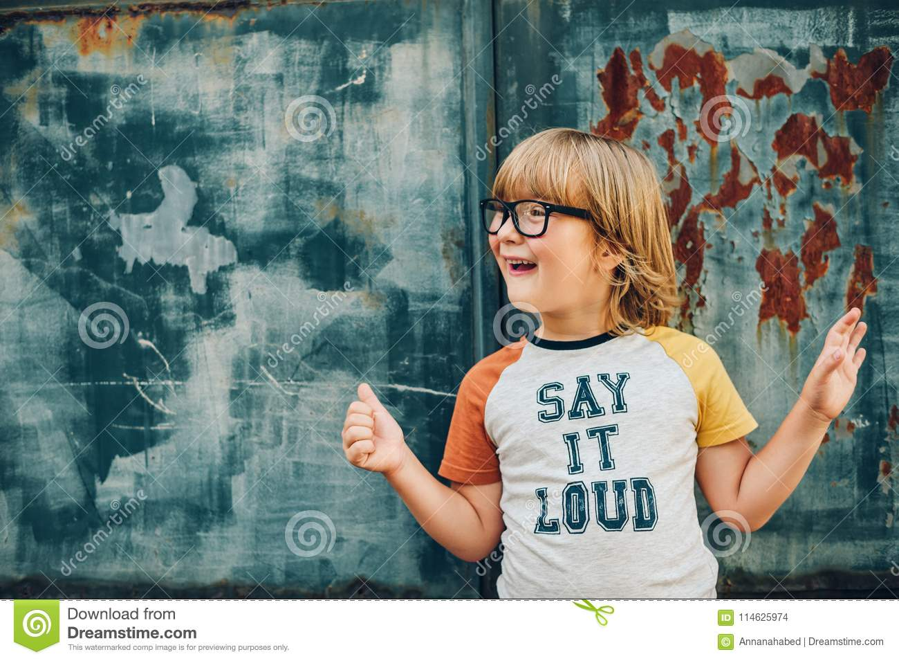 bea90915fafc Outdoor portrait of funny little boy wearing glasses and t-shirt with sign  `Say It Loud`
