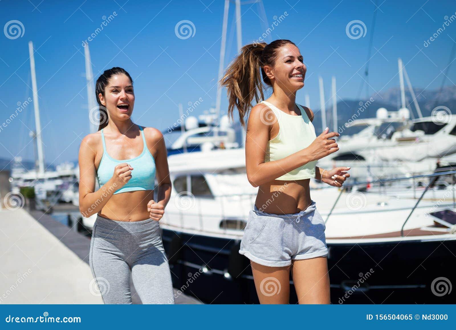 Outdoor portrait of group of happy fit women running