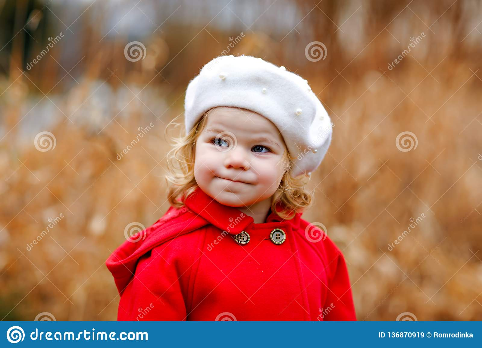 fbdeade7e0e Outdoor portrait of little cute toddler girl in red coat and white fashion  hat barret.