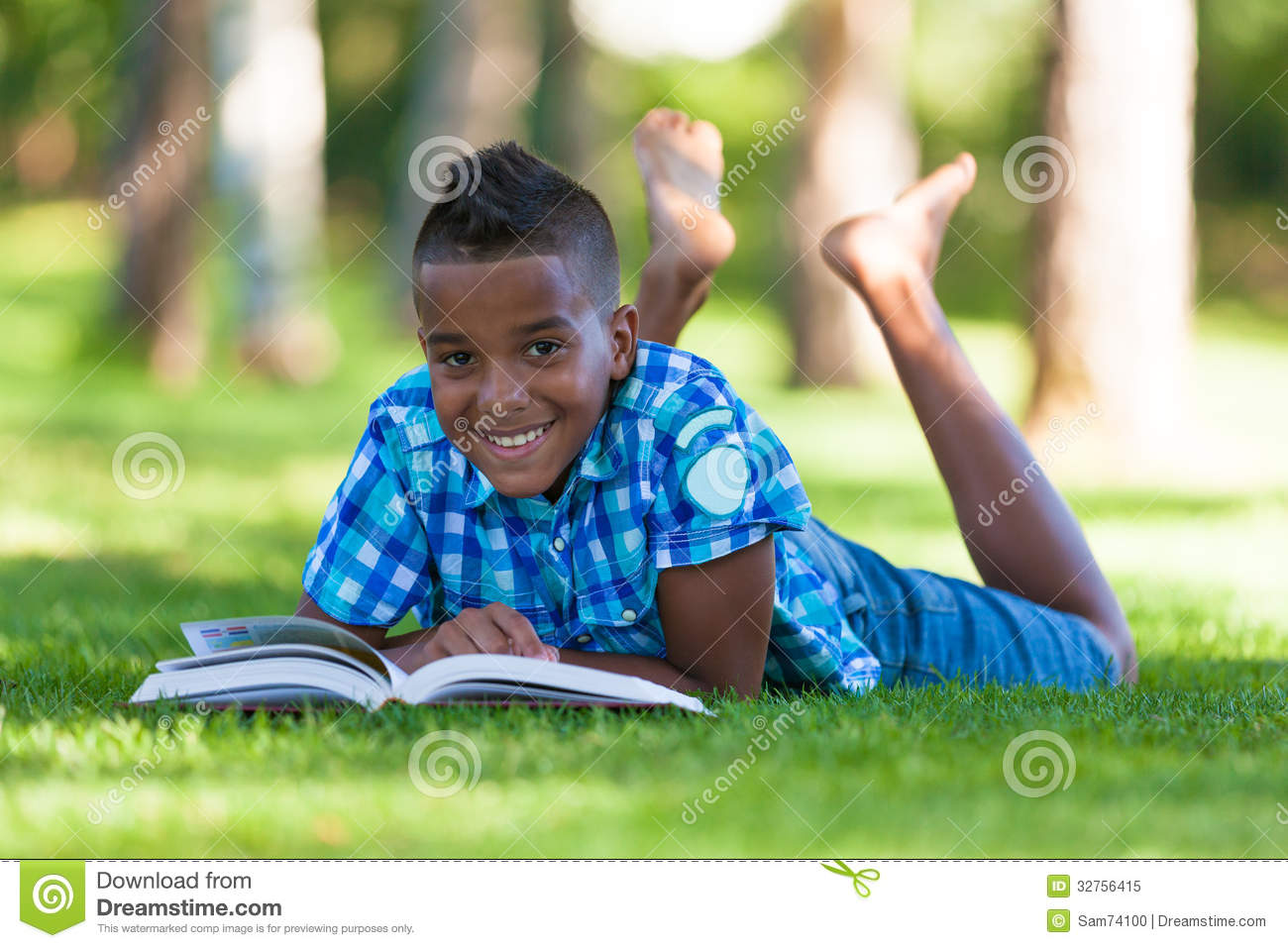 Outdoor portrait of student black boy reading a book
