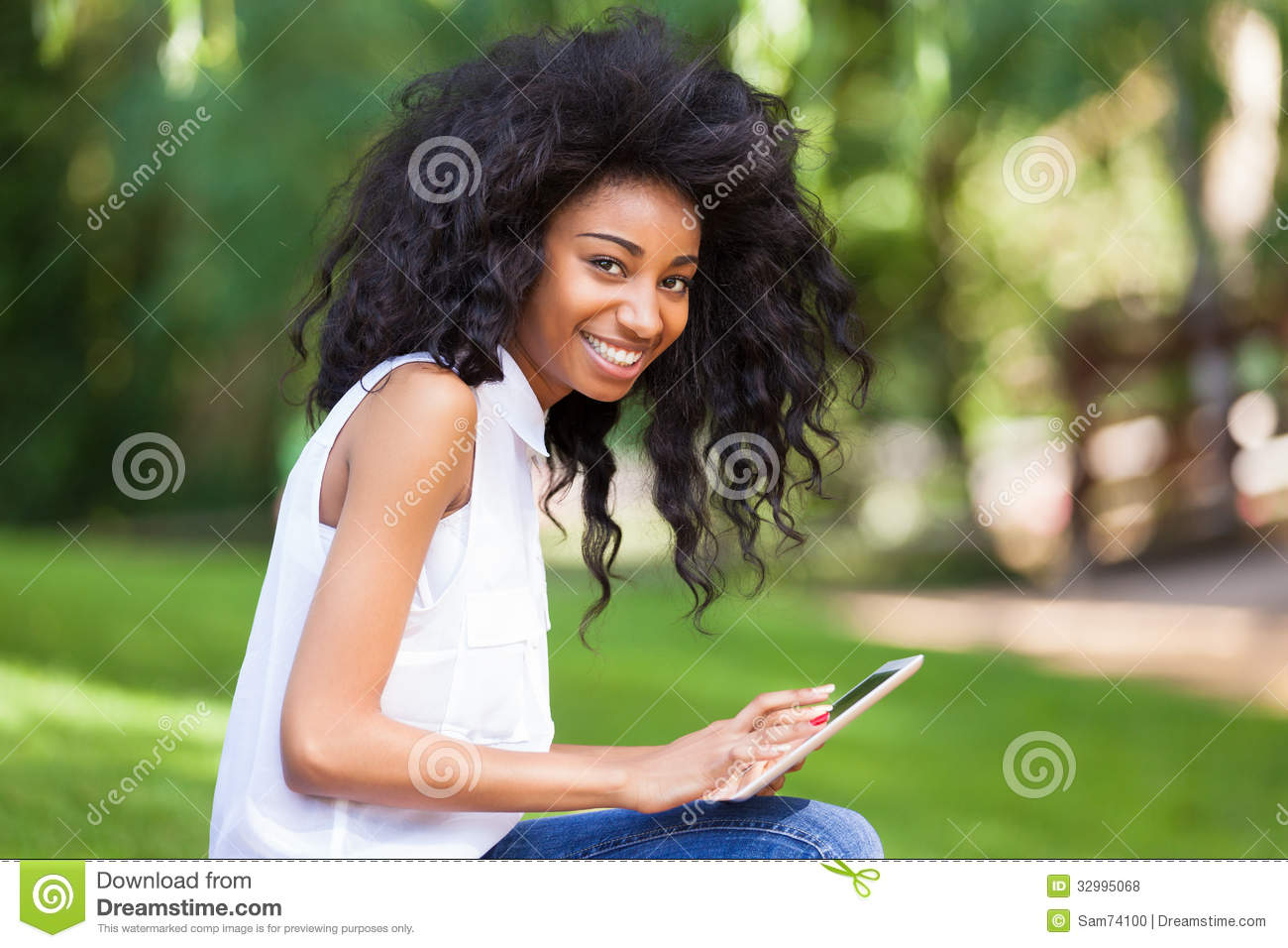 Outdoor Portrait Of A Teenage Black Girl Using A Tactile